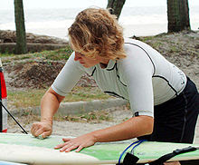Photo of man bent over surfboard rubbing bar of solid wax against the board with palm trees and ocean in background