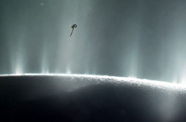 An artist's concept of NASA's Cassini spacecraft flying through plumes of water vapor erupting from the surface of Saturn's moon Enceladus.