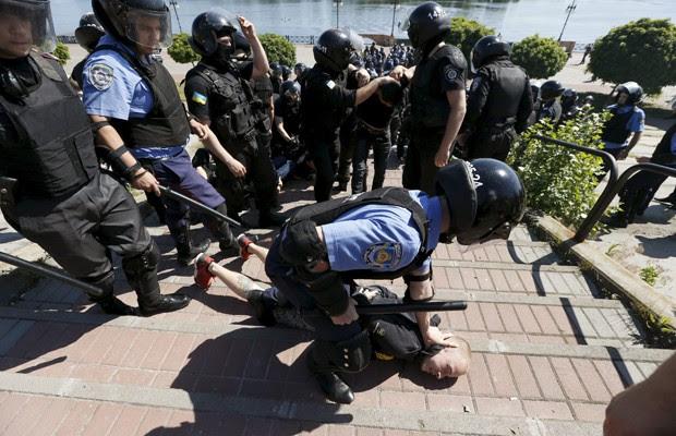 Membro da guarda do Ministéio do Interior prende manifestante antigay durante marcha pela igualdade em Kiev, neste sábado (6) (Foto: Reuters)