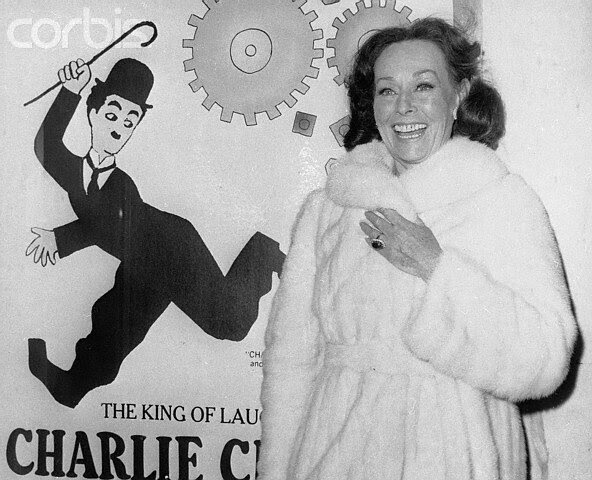 Paulette Goddard Posing in Front of a Charlie Chaplin Poster