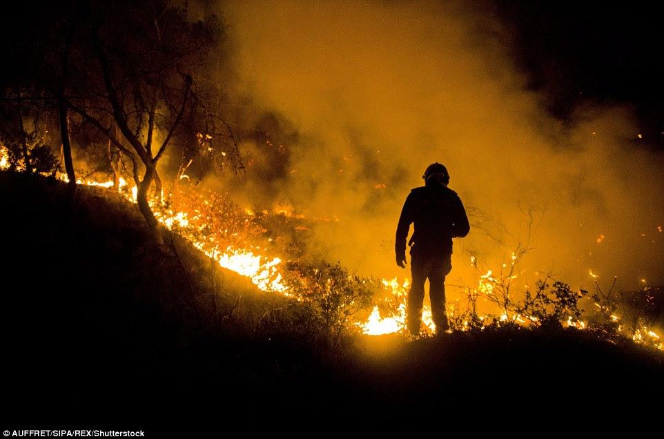 Um bombeiro parece estar quase andando em chamas nesta imagem dramática