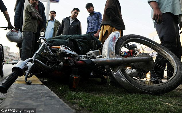 Pakistani people look at the motorbike of a man who was killed in the shooting yesterday