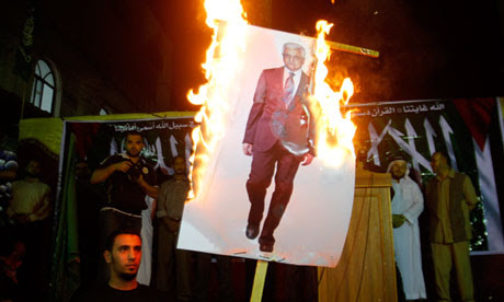Palestinian refugees burn an image of Mahmoud Abbas