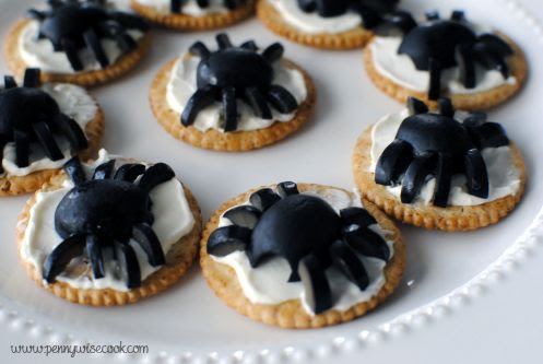 Olive spiders on cream cheese and cracker. Healthy yet spooky.