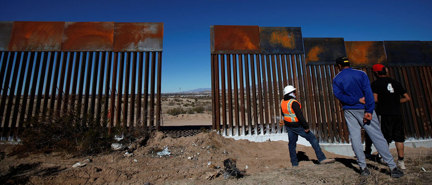 A worker chats with residents at a newly built section of the U.S.-Mexico border fence at Sunland Park, U.S. opposite the Mexican border city of Ciudad Juarez, Mexico January 26, 2017. (PHOTO: REUTERS/Jose Luis Gonzalez)