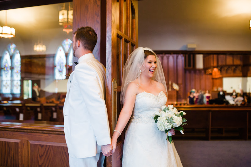 The bride and groom holding hands on either side of a door before their wedding Court Street United Methodist Church in downtown Rockford Illinois for an Autumn wedding.