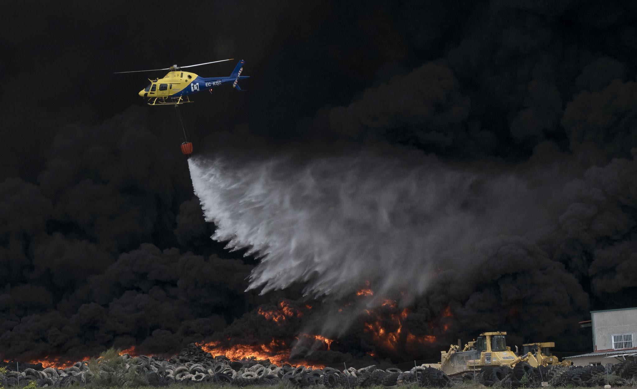 A helicopter drops water over tyres burning in an uncontrolled dump near the town of Sesena, after a fire brokeout early on May 13, 2016.   A huge waste ground near Madrid where millions of tyres have been dumped was on fire today, releasing a thick black cloud of toxic fumes that officials worry could harm residents nearby.