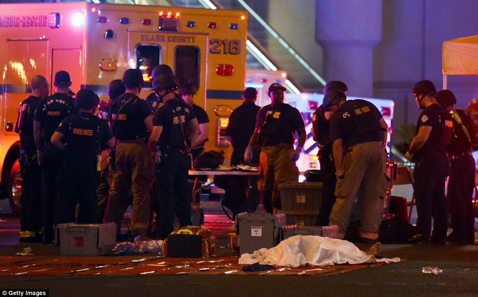 A body lies under a sheet on The Strip in Las Vegas as police secure the area after 58 people were killed on Sunday