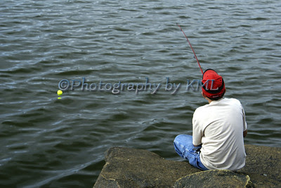 teen fishing at the ocean wearing jeans