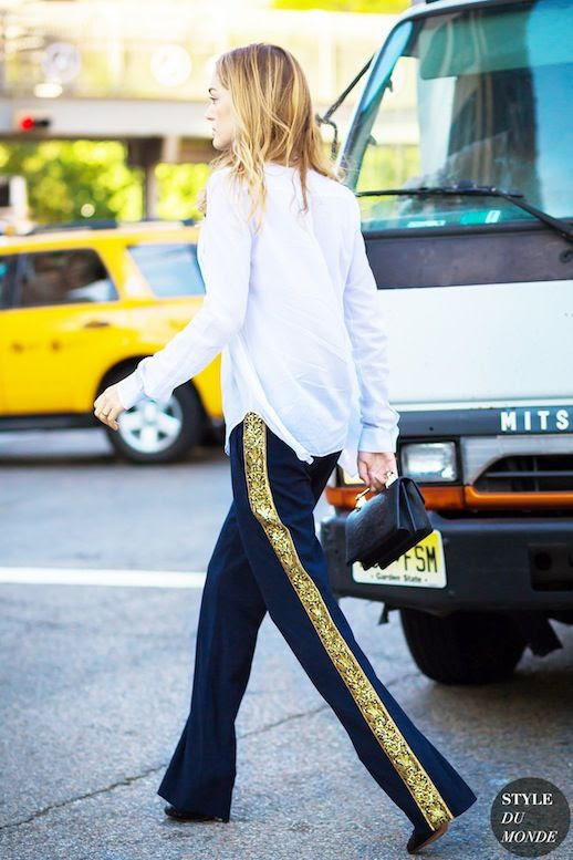 Le Fashion Blog Street Style White Top Black Clutch Blue And Gold Side Stripe Pants Via Style Du Monde