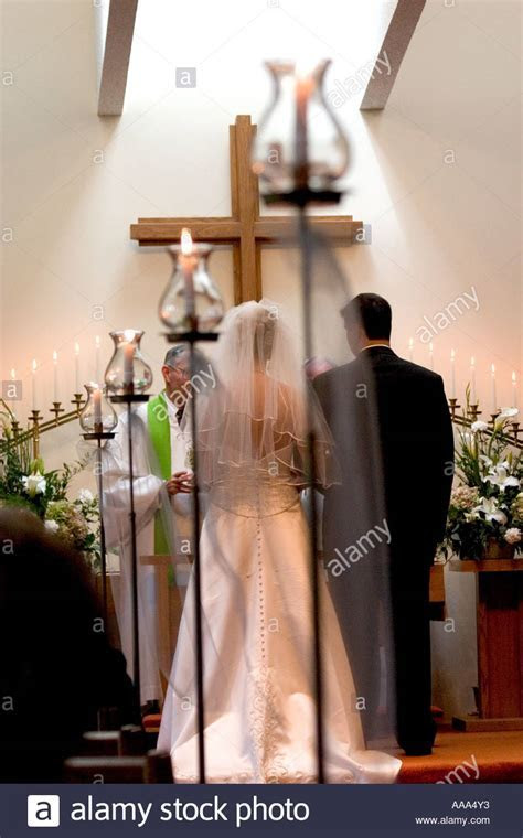 Bride and groom exchanging wedding vows at church alter