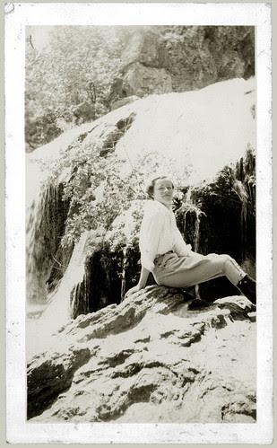 Girl on a rock beside a waterfall