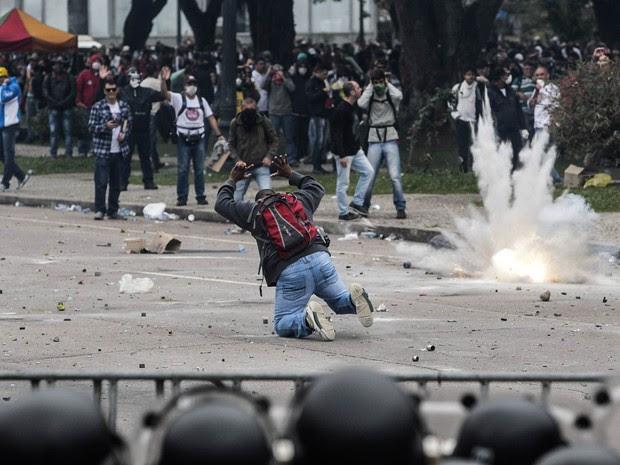 Bomba atirada pela polícia explode ao lado de um manifestante durante ação da polícia para dispersar o protesto em Curitiba (PR) (Foto: Daniel Castellano/Agência Gazeta do Povo)