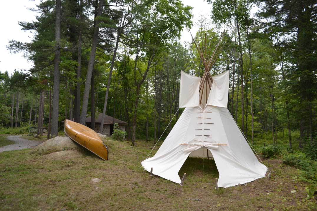 A traditional Anishinaabek teepee and canoe are positioned along one of the park's trails.