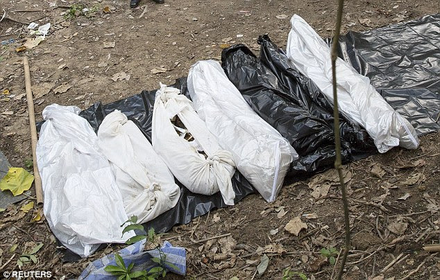 Corpses: Authorities believe identifying the dead bodies (pictured) will be a lengthy process because relatives  need to travel from Myanmar and Bangladesh to give DNA samples