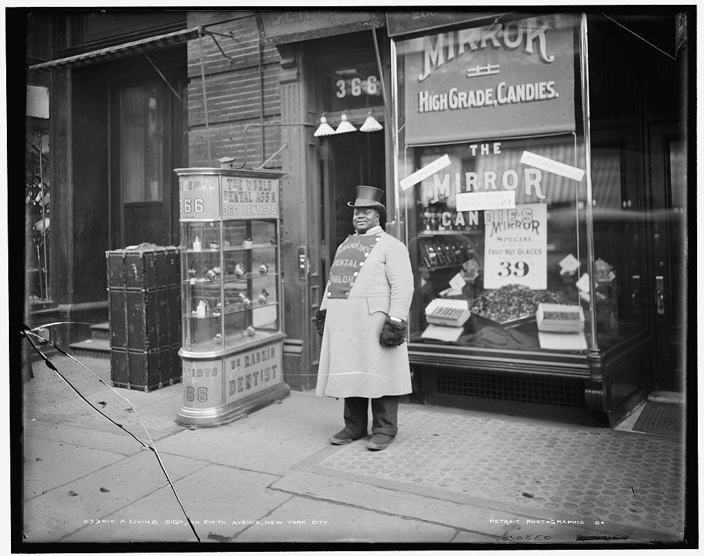 A man stands outside shops at 34th Street and 5th Avenue.