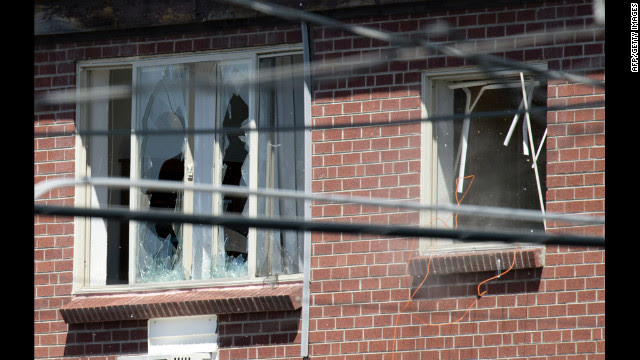 Debris flies out a window, right, after law enforcement officers detonate an explosive device inside the apartment Saturday.