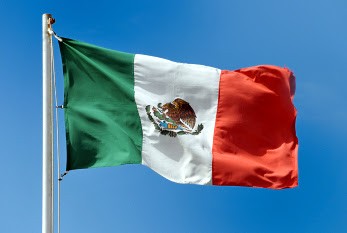Mexican national flag waving in the wind against the sky.