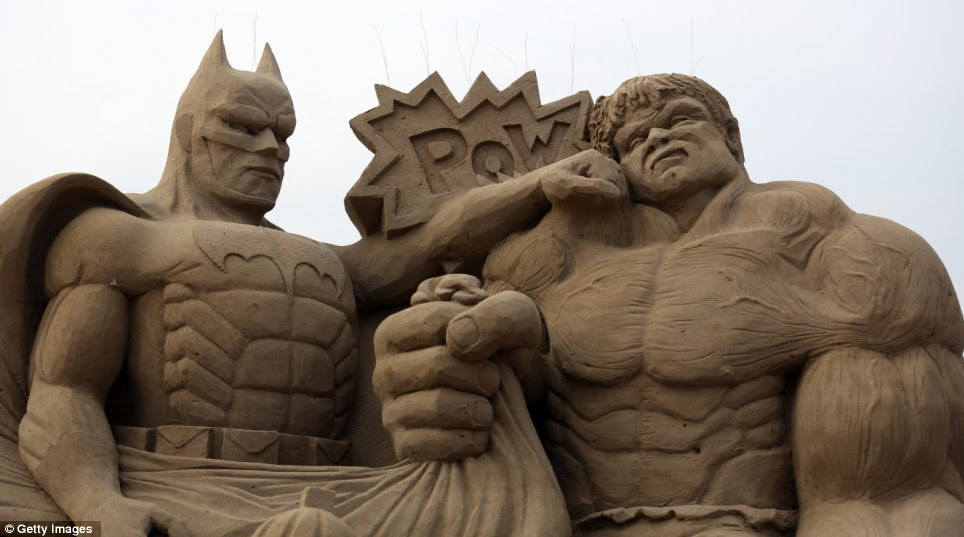 Super sculptures: Batman and The Incredible Hulk flex their muscles on the beach trying to impress the Hollywood totty, such as Marylin Monroe, surrounding them