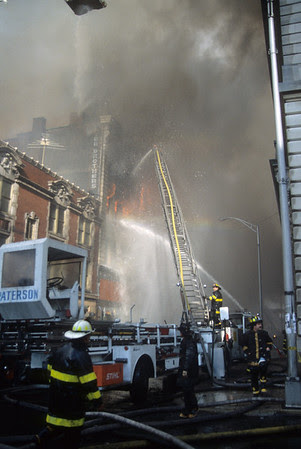 Paterson Ladder Co.3 operates on Washington St. looking north from the corner of Ellison St as heavy fire consumes the 4th floor of exposure C.