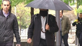 Joaquín Benítez arribant a la Ciutat de la Justícia amagant el rostre amb gorra, tapaboques i paraigua