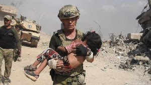 "These photos are courtesy of Free Burma Rangers (www.freeburmarangers.org/) Credit needed.  The photos were taken in western Mosul while members of ""Free Burma Rangers"" were helping Iraqi civilians escape areas controlled by ISIS.  David Eubank & girl in pink 2 David Eubank from the ""Free Burma Rangers"" carries a little girl to safety after spotting her hiding under her mother's hijab for two days. They used a tank for cover and the he moved out to save her."