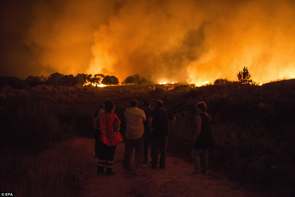Residents of Vilardevos village observe a forest fire in Verin where authorities activated 'situation 2' alert due to the closeness to population centers and main roads