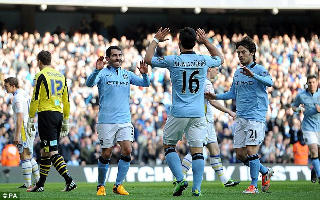 Three and easy: Carlos Tevez celebrates with Aguero and David Silva after scoring City's third goal
