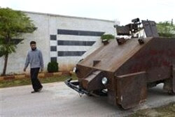 A Syrian rebel walks past Sham II, a homemade armoured vehicle made by the rebels' Al-Ansar brigade