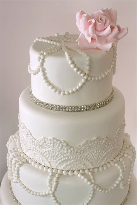 Elegant white vintage wedding cake with pearls, lace and