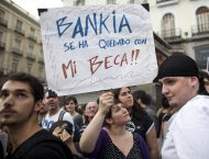 """A demonstrator holds up a sign reading """"Bankia took my scholarship"""" in the Puerta del Sol square during a protest marking the one year anniversary of Spain's Indignados  movement in Madrid, May 12, 2012. Dubbed """"los indignados"""" (the indignant), the movement which spawned similar protests worldwide, has called for 96 hours of continuous protest to culminate at the Puerta del Sol square where the movement was founded a year ago in a renewed protest over government austerity measures, banks, politicians, economic recession, and the highest unemployment in the eurozone.    REUTERS/Paul Hanna (SPAIN - Tags: CIVIL UNREST POLITICS SOCIETY)"""