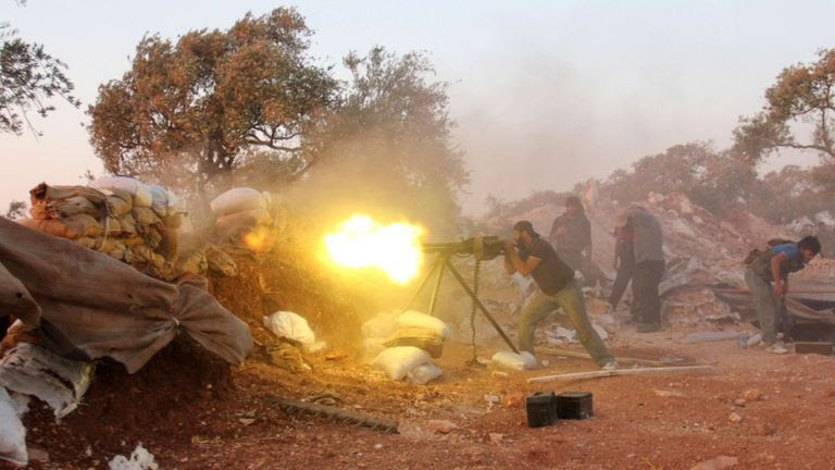A rebel fighter fires heavy artillery during clashes with government forces in Idlib province