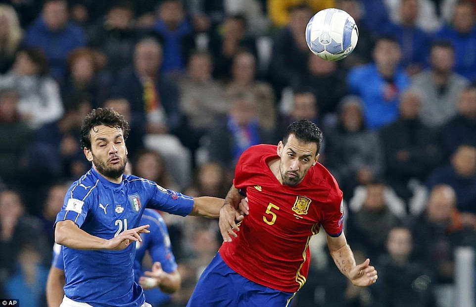 Sergio Busquets of Spain and Italy's Marco Parolo compete in an aerial battle during a goalless first half