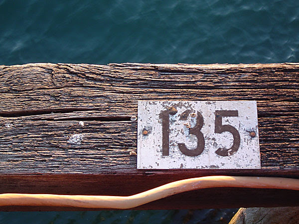 Sign reading 135, on a weathered piece of wood