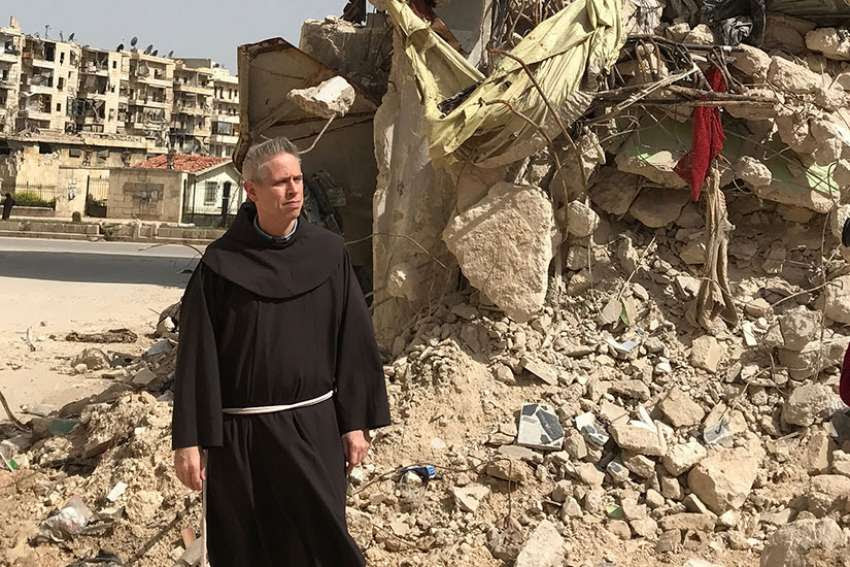 Father Michael Perry, minister general of the Franciscans, walks past the rubble of a bombarded building in Aleppo, Syria, during an early April visit to Franciscan friars there.