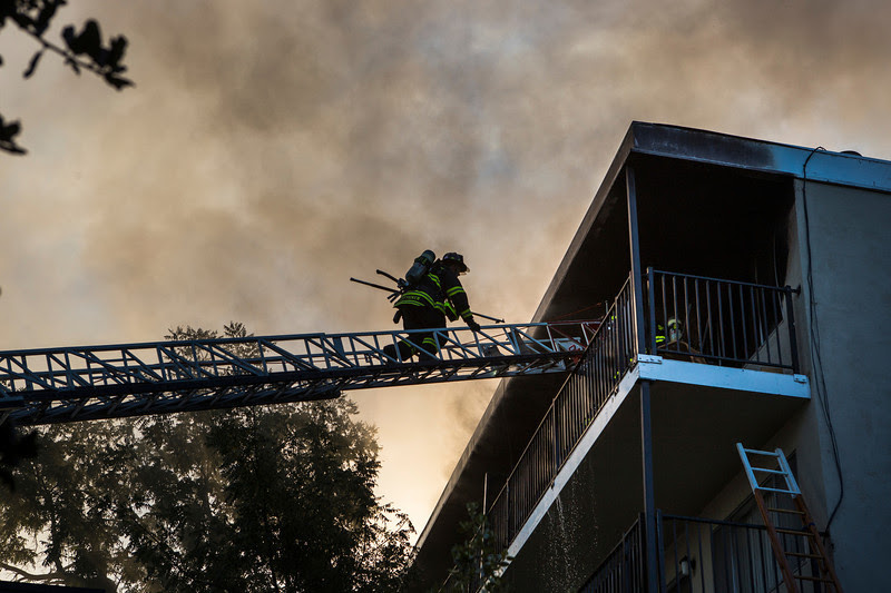 Fire crews battle a six-alarm fire at a apartment building in Redwood City, Calif., on Thursday, Oct. 17, 2013. The fire was reported shortly after 5:15 a.m. at a four-story, 75-unit apartment building on the 900 block of Woodside Road. As of 9 a.m., Redwood City Fire Marshal Jim Palisi said the fire was nearly out but that there were still some hot spots.  (John Green/Bay Area News Group)