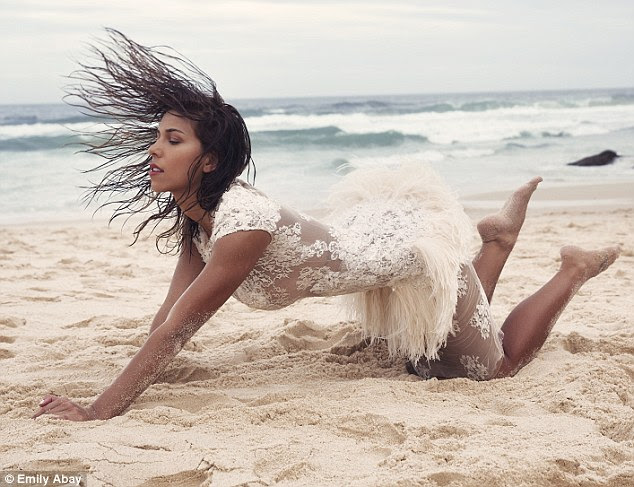 Leaping in to it: Devin posed in another frame with her knees on the sand and flipping her brunette locks