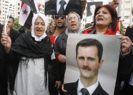 Pro-Syrian regime protesters, shout pro-Syrian President Bashar Assad slogans as they gather outside the Syrian foreign ministry where Syrian Foreign Minister Walid al-Moallem helds a press conference, in Damascus, Syria, on Monday Nov. 14, 2011. Syria's foreign minister accused Arab states on Monday of conspiring against Damascus after the Arab League voted to suspend Syria's membership over the government's deadly crackdown on an eight month-old uprising. (AP Photo/Muzaffar Salman)