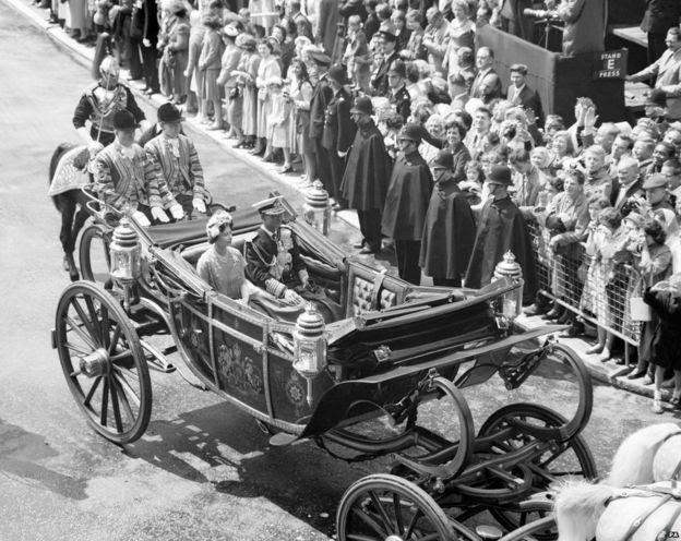Người dân và cảnh sát đứng dưới trời mưa chào đón Quốc vương Bhumibol của Thái Lan và Nữ hoàng Anh khi họ đi từ Victoria tới Cung điện Buckingham ở đầu chuyến thăm Anh Quốc năm 1960