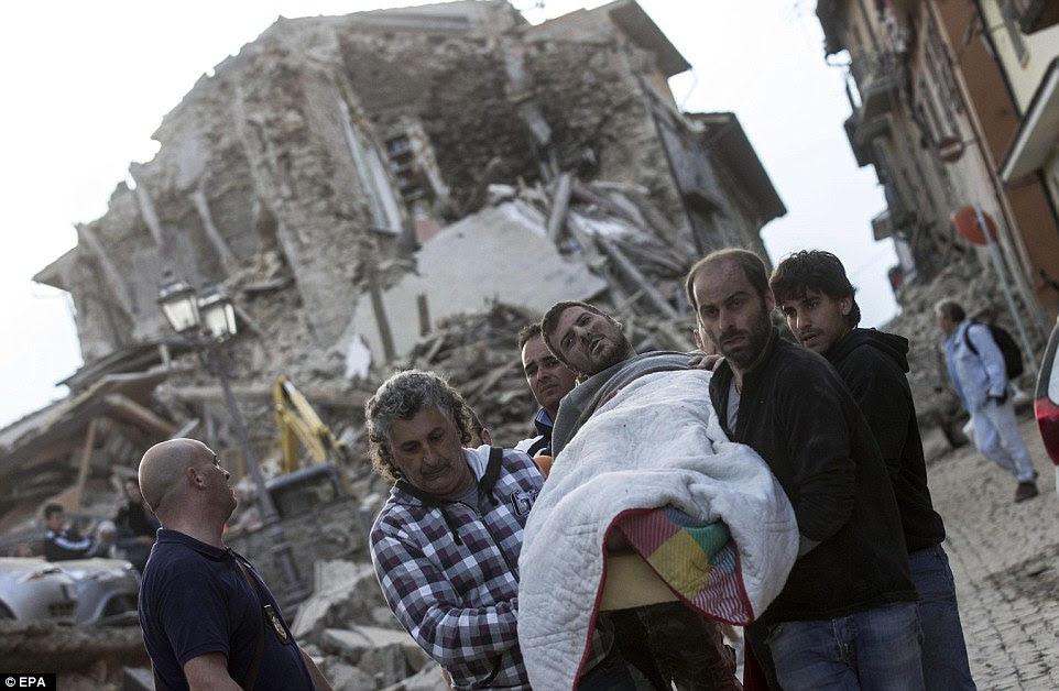 Na dor: Um homem ferido é transportado em um cobertor depois de ser salvo dos escombros de um prédio desmoronado em Amatrice