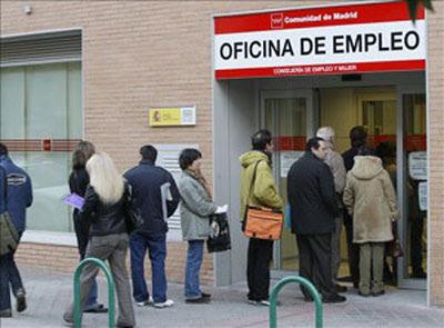 Varias personas hacen cola ante una oficina de empleo.