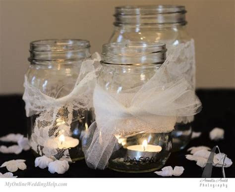 Mason jars with lace and scattered petals looks elegant