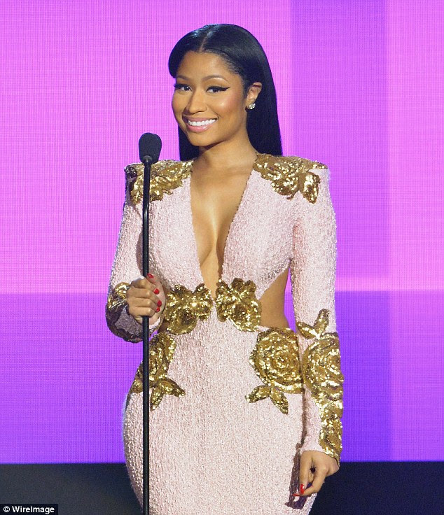 Pretty in pink: Nicki Minaj wowed in a cut-out gown as she picked up two awards at the American Music Awards on Sunday