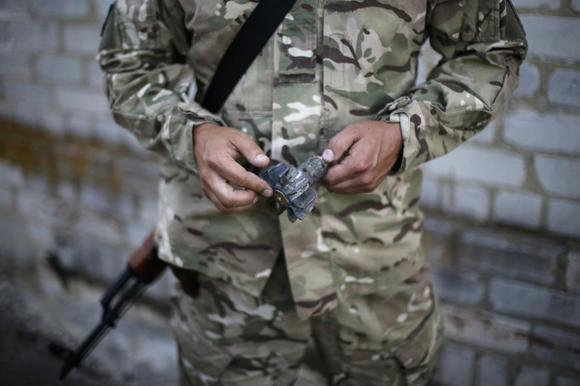 A Ukrainian serviceman holds a piece of a mortar projectile in his camp near Donetsk September 2, 2014. REUTERS/Gleb Garanich