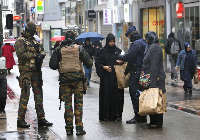 Belgian soldiers and a police officer control the documents of a woman in a shopping street in centr
