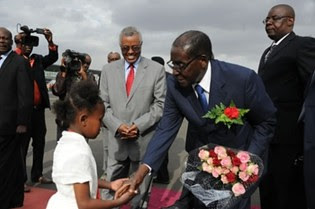 Republic of Zimbabwe President Robert Mugabe receives flowers from Ethiopian child when arriving for the African Union Summit in Addis Ababa, Ethiopia on January 28, 2014. by Pan-African News Wire File Photos