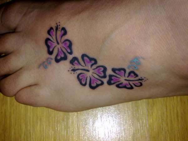 Girl Hibiscus Flowers Tattoo On Left Foot