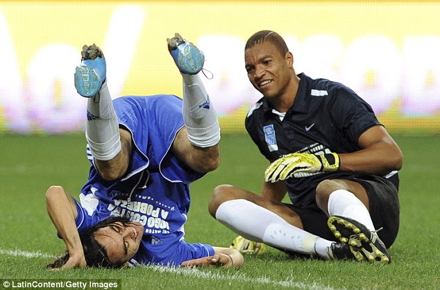 Rough and tumble: Goalkeeper Dida smiles as Sorin goes rolling by