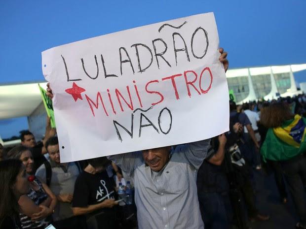 Manifestante ergue cartaz em protesto contra a nomeação do ex-presidente Lula como ministro da Casa Civil, em frente ao Palácio do Planalto (Foto: Eraldo Peres/AP)