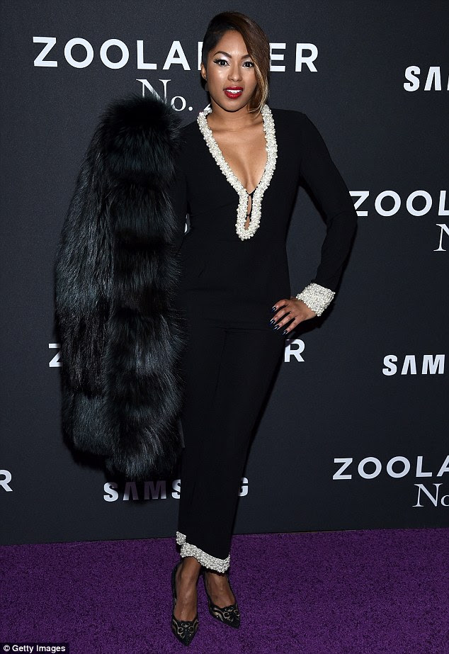 Camera ready: Journalist Alicia Quarles looked super chic in a black one-piece with beaded trims and fur coat
